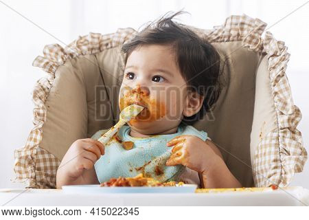 Adorable Little Child Funny Girl Eating Spaghetti With Spoon While Sitting In High-powered Chair At