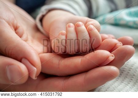 Family Baby Hands. Closeup Of Baby Hand Into Parents Hands. Father And Mother Holding Newborn Kid. F