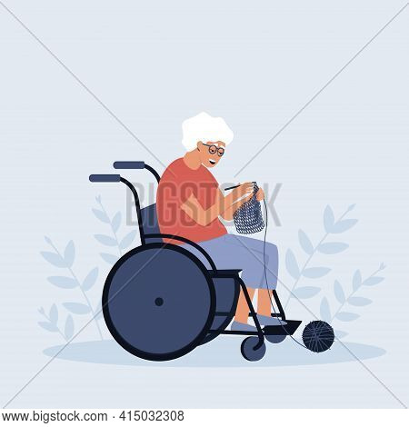 An Elderly Woman In A Wheelchair Is Crocheting. A Pensioner In A Wheelchair. A Hobby For Many Women