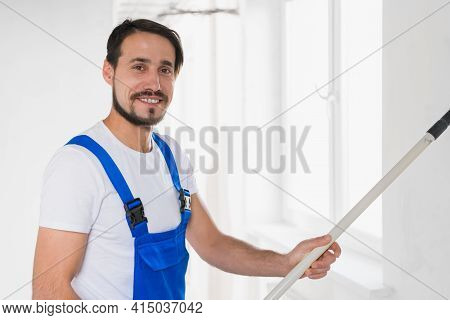 Handsome Man In Overalls Paints The Wall With A Roller
