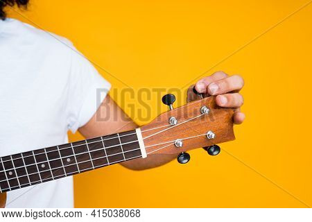 Close-up Photo. Male Hands Tuning And Playing Small Guitar On Yellow Background