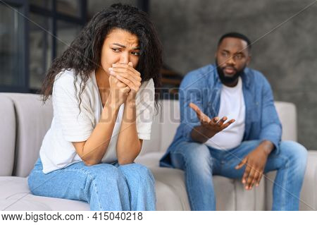 Frustrated Crying Biracial Woman Sits On The Foreground, Depressed And Unhappy, An African-american