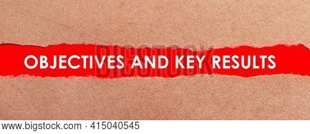 A Strip Of Red Paper Under The Torn Brown Paper. White Lettering On Red Paper Objectives And Key Res