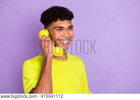 Photo Portrait Of Young Curly Guy Talking On Phone Looking Copyspace Holding Landline Isolated On Pa