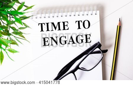 Time To Engage Is Written In A White Notebook Next To A Pencil, Black-framed Glasses And A Green Pla