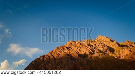 Rocky Outcrop At Sunset Against Clear Blue Sky.