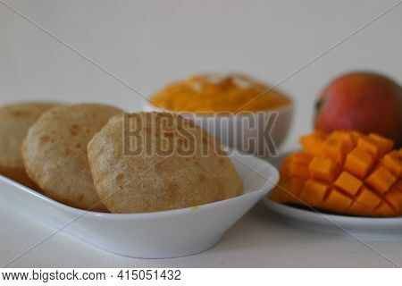 Puri Served With Mango Pulp Locally Known As Aamras. Mango Pulp Is Made From Lalbagh Mango