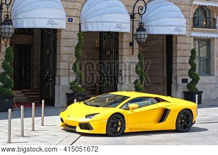 Paris, France, June 22: A Bright Yellow Car Is Parked Outside The Front Entrance Of The Ritz Hotel O
