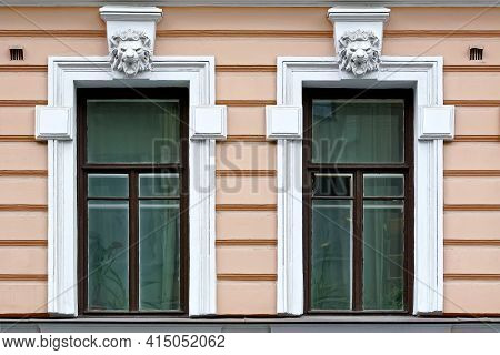 Two Rectangular Windows With A Bas-relief On The Background Of A Pink Stucco Wall. From The Windows