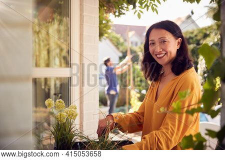 Portrait Of Mature Asian Woman Planting Plants Into Wooden Garden Planter At Home