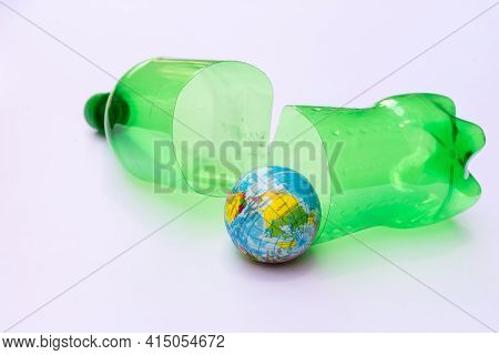 Concept Of Reflecting The Problem Of Global Warming Pollution. Split Green Plastic Bottle Are Going