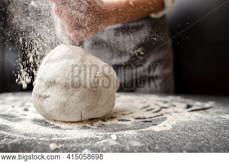 Large Lump Of Kneaded Dough Lying On The Table Is Sprinkled With Flour. Baker Prepares Bread.