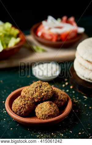 closeup of an earthenware bowl with some falafel, some chopped lettuce, onion and tomato in some plates and a pile of pita breads, on a rustic green wooden table
