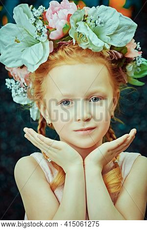 Close-up portrait of a cute red-haired girl with radiant gray-blue eyes and a slight smile in a wreath of flowers. Beauty. Easter holiday. Childhood. Spring-summer season.