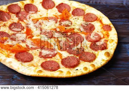 Closeup of pepperoni pizza with salami mozzarella and tomatoes on wooden table. Selective focus.