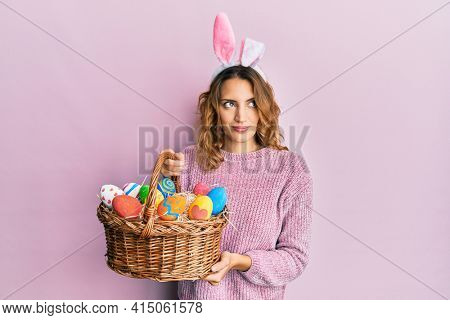 Young caucasian woman wearing cute easter bunny ears holding colored egg smiling looking to the side and staring away thinking.
