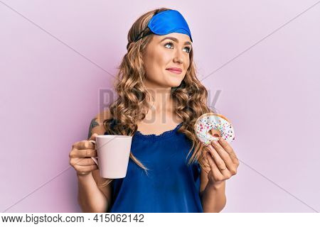 Young blonde girl wearing sleep mask and pyjama having breakfast smiling looking to the side and staring away thinking.