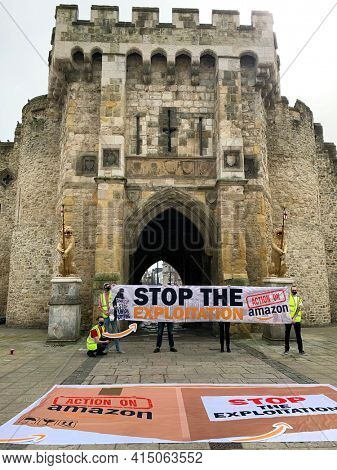 Southampton, UK - 31th March 2021: A group of protesters hold up a banner outside of the Southampton Bargate,. The banner reads Stop the Explotation, Amazon stop Union busting, Action on Amazon.