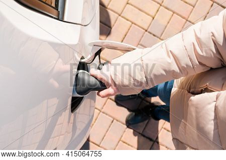 Top View Of Woman Hand Inserting The Power Cable Supply Plugged Into The Electric Car For Recharging