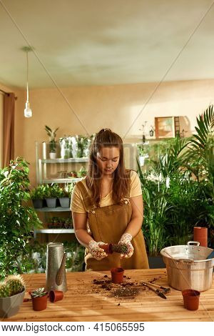 Young Girl Farmer In Overalls Standing Over The Table In The Home Garden. Home Garden Concept. Trans