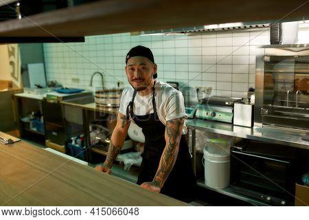 Man Standing In The Kitchen And Smiling At The Camera. Asian Food Concept. Young Chef Standing In Th