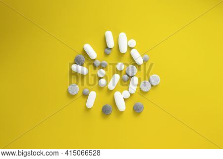 Pills And Tablets On Yellow Background. Vitamins And Supplements Concept