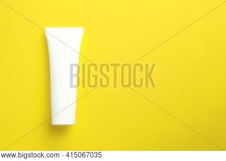 Cosmetic Cream In White Tube On Yellow Background With Copy Space. Skincare Mockup Concept