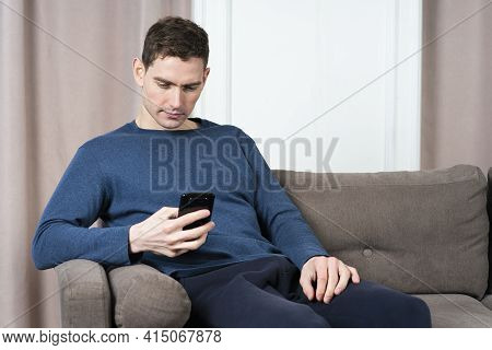 Handsome Serious Guy, Young Man Is Sitting On Couch Of Sofa In Living Room At Home And Looking At Sc