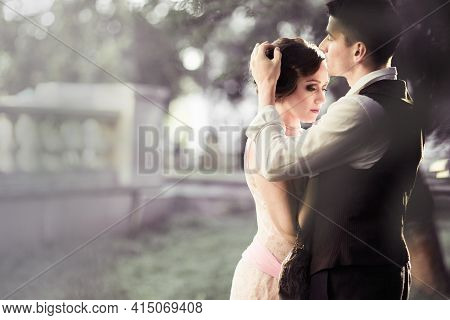 Couple In Retro Dress Stands Against A Large Trees And A Fence. A Man Adjusts The Hair On A Womans H