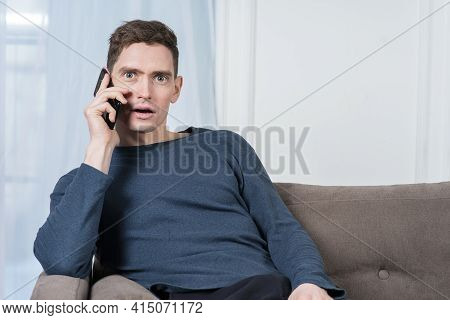Portrait Of Surprised Shocked Guy, Handsome Young Man With Wide Open Eyes And Mouth Is Talking On Ce