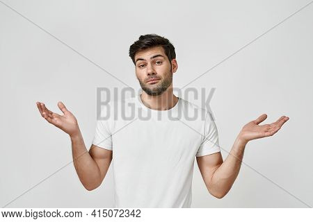 Do Not Understand What Is Happening. Portrait Of A Young Bearded Man Wearing T-shirt Spreading His A
