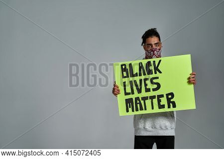 Young Gypsy Man In Buff Holding Anti Racism Placard And Looking At Camera While Posing On Light Back