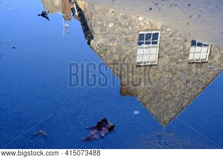 Old Stone Building With Two Windows In Winchester Reflected In A Puddle After Rain With Blue Sky Sho