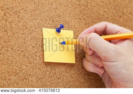 A Man Writing On A Paper Note With A Ballpoint Pen That Is Pinned On A Cork Board. Close Up.