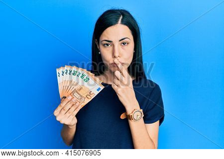 Beautiful young woman holding bunch of 50 euro banknotes mouth and lips shut as zip with fingers. secret and silent, taboo talking