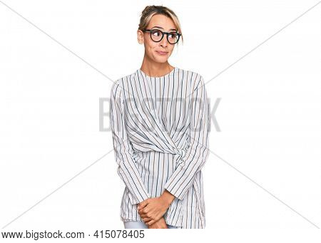Beautiful blonde woman wearing business shirt and glasses smiling looking to the side and staring away thinking.