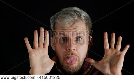 Comical Stupid Stylish Man With Blue Eyes, Hiding Behind Hands, Making Funny Awkward Silly Face Grim