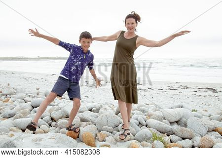 Happy Playful Family Have Fun On The Beach. Young Mother And Son Run And Jump At Sunset On Ocean Coa