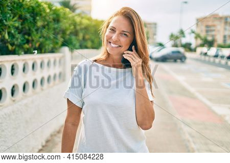 Beautiful middle age hispanic woman smiling speaking on the phone happy outdoors