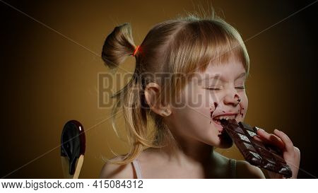 Joyful Child Kid With Dirty Face From Melted Chocolate On Dark Background In Studio. Satisfied Teen