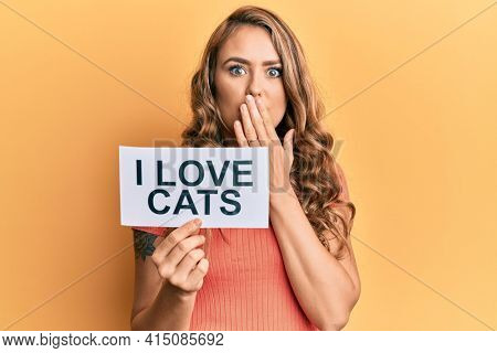 Young blonde girl holding paper with i love cats phrase covering mouth with hand, shocked and afraid for mistake. surprised expression