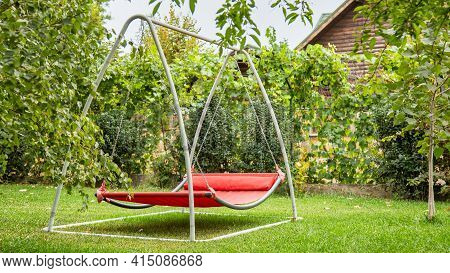 Red Hammock Swing In Metal Frame With Nobody On Green Lawn In Backyard Near Log House Cottage. Rest
