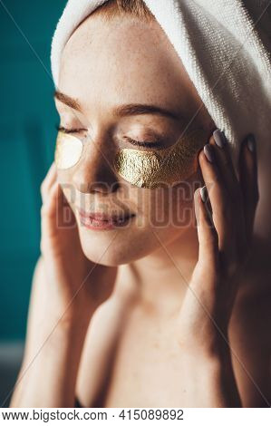 Ginger Woman With Freckles Is Applying Hydrogel Eye Patches While Wearing A Towel On Head
