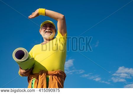 Elderly Man Practicing Sports On Blue Sky Background. Sporting. Healthy And Sport. Grandfather Pensi