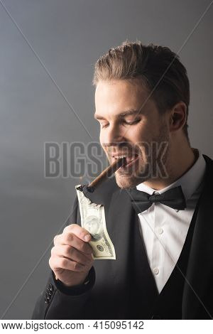 Wealthy Businessman Lighting Cigar With Hundred Dollar Banknote On Grey Background With Smoke.