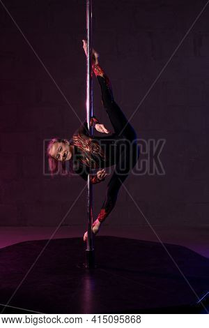 Graceful Girl Doing Gymnastic Exercise Near Pole In Darkness