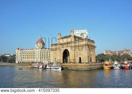 MUMBAI, INDIA - JANUARY 11, 2017: Taj Mahal Palace Hotel and Gateway of India. Both structures in Mumbai Harbor overlook the Arabian Sea.