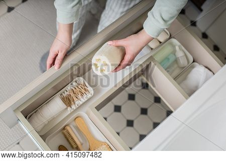 Top View Female Housewife Organizing Bathroom Amenities And Toiletries In Open Drawer Under Sink