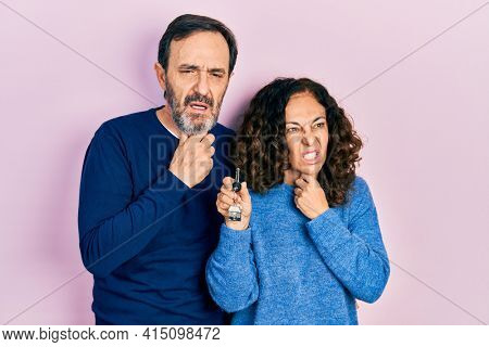 Middle age couple of hispanic woman and man holding keys of new home touching painful neck, sore throat for flu, clod and infection