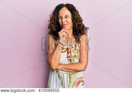 Middle age hispanic woman wearing casual clothes thinking concentrated about doubt with finger on chin and looking up wondering